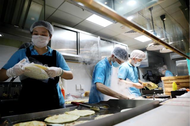 在上海地铁13号线世博会博物馆地铁站附近的一家盒小马服务点,工作人员在制作煎饼果子等早餐餐品(7月17日摄)。新华社图。