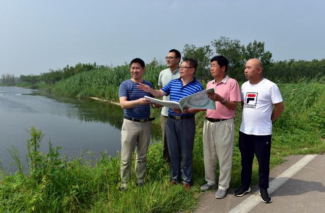 8月11日,山东省德州市齐河县祝阿镇省派乡村振兴服务队成员与贾坊村干部们在研究文化旅游产业发展规划。摄影/章轲