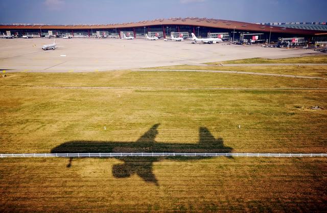 9月24日,一架国航班机即将降落在首都国际机场T3航站楼。摄影/章轲