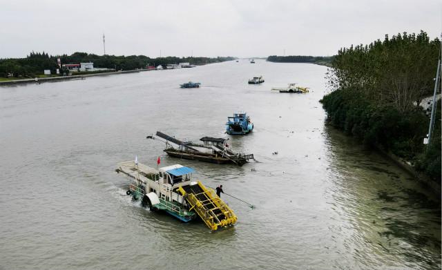 10月15日,苏浙沪三地的保洁船在太浦河水域联合清理水面浮游植物(无人机照片)。新华社图。