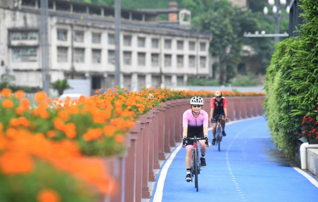 7月23日,市民在重庆市江北区北滨路漫走步道的自走车道上骑走。新华社图。