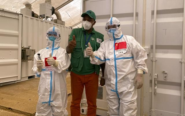9月2日,在几内亚首都科纳克里一个核酸检测取样点,中国抗疫医疗专家组成员与当地工作人员合影。新华社发
