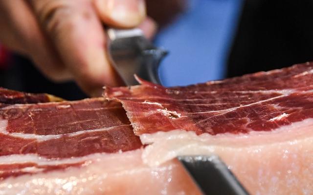 11月6日,在进博会食品及农产品展区,一展台的工作人员在切火腿片。