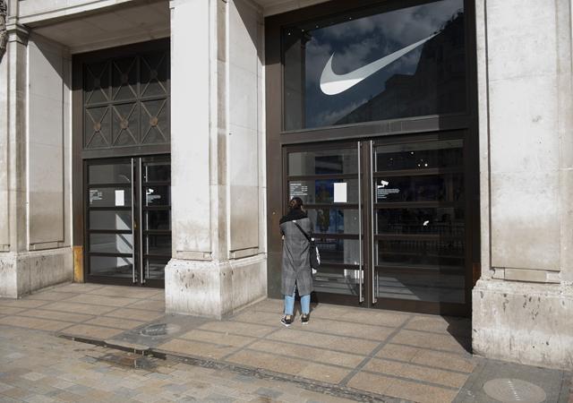 去年3月,在英国伦敦,别名女子浏览一家耐克商店门口贴出的休憩交易告示。新华社原料