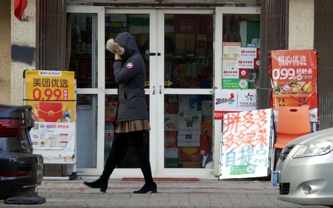 社区团购正激战。| 图片来源:视觉中国——2020年12月19日,天津,一市民从超市前美团旗下的美团优选、拼多多旗下的多多买菜、滴滴旗下的橙心优选社区电商宣传海报旁走过。