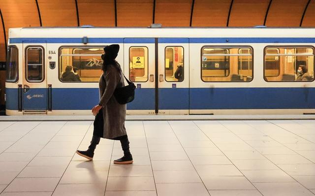在德国慕尼黑,一名戴口罩的女子从地铁车厢前走过。