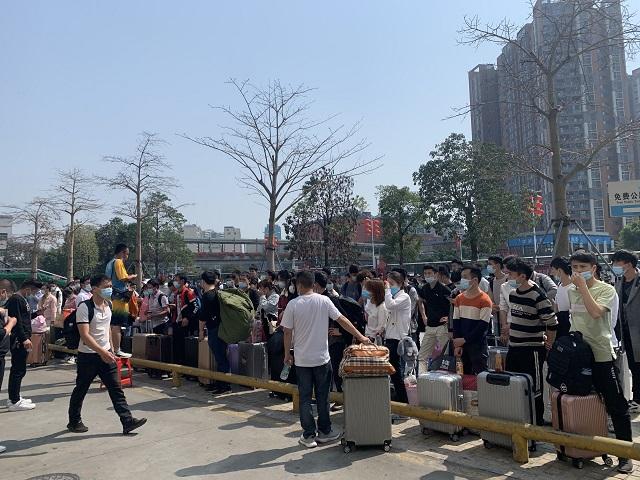 深圳龙华汽车站广场上准备进厂的人们。黄琼/摄