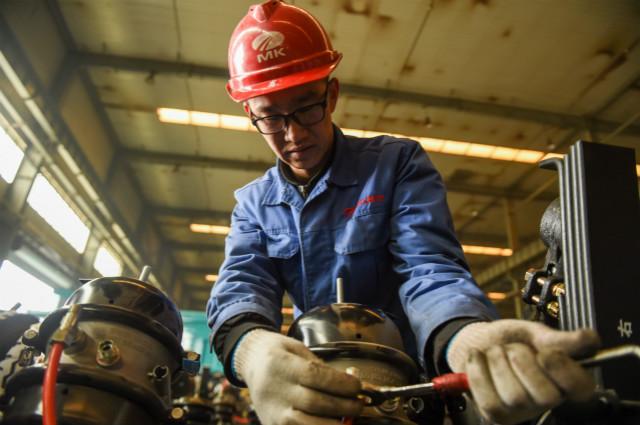 3月17日,在鄂尔多斯装备制造工业园区内,一家特种车辆制造有限责任公司的工人调试设备。新华社图。