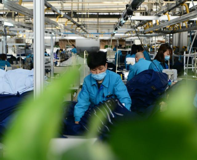 2021年2月5日,在井陉县际华三五零二职业装有限公司,工人在服装车间生产线上工作。新华社图。