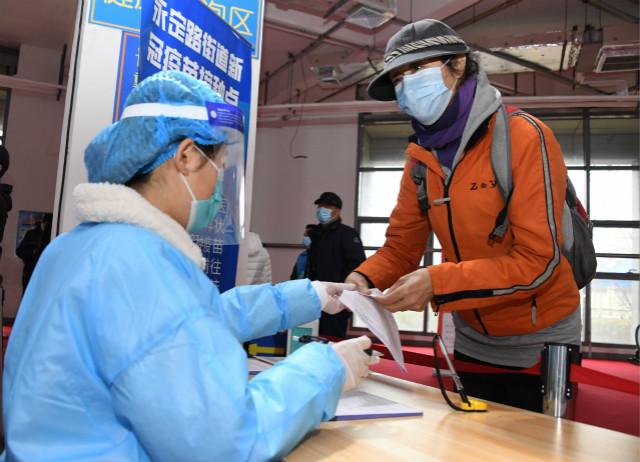 3月14日,在北京市海淀区永定路街道新冠疫苗临时接种点,社区居民(右)询问医护人员接种注意事项。新华社图。