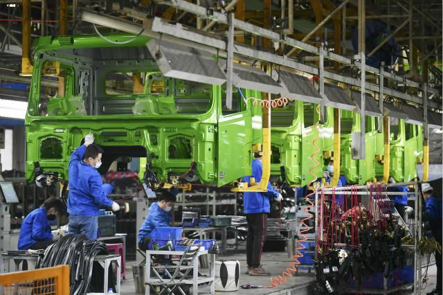工人在位于西安的陕西汽车控股集团有限公司重卡总装线上作业(2月24日摄)。新华社图。