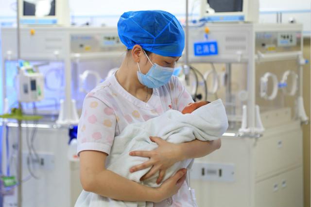 2020年5月11日,贵州省余庆县人民医院新生儿科护士长冉晴在护理新生儿。新华社图。