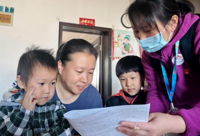 2020年11月10日,北京市丰台区东高地街道万源南里社区的普查人员在居民家中进行普查登记。新华社图。