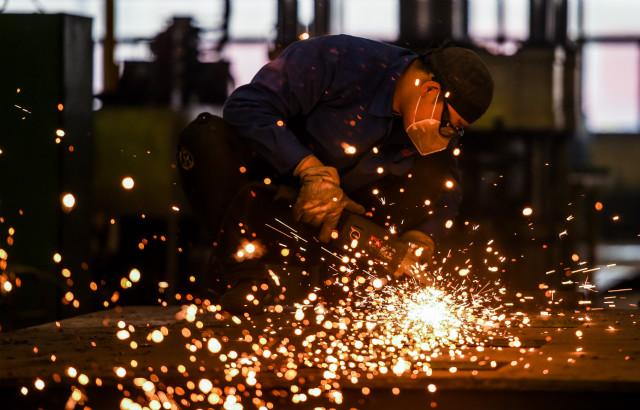 3月17日,在鄂尔多斯装备制造工业园区内,一家特种车辆制造有限责任公司的工人在切割钢板。新华社图。