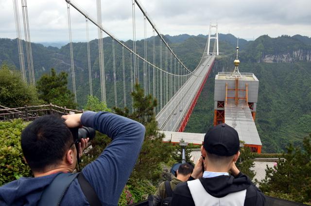 """22日,参加""""沿着高速看中国——红色之旅""""主题采访的媒体记者们在拍摄矮寨大桥。摄影/立早"""