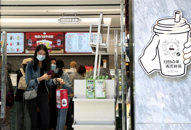 2020年10月8日,游人从上海豫园一家饮品店走出。新华社图。