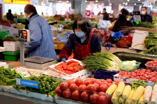 3月20日,合肥市华府骏苑菜市场的商家在整理摊位。新华社图。