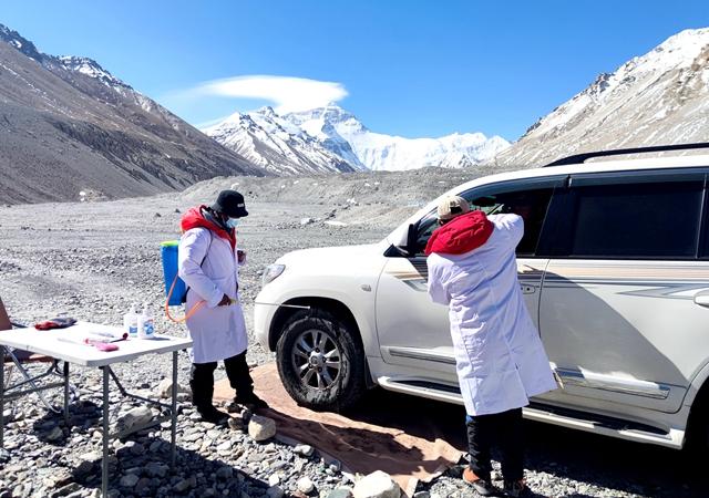 5月9日,大本营外防疫卡点的工作人员为进入营地的工作车辆消毒,并为驾驶员量体温。