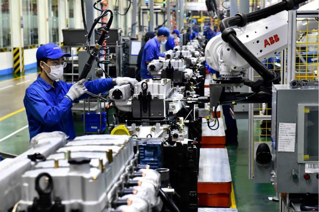 4月22日,在位于山东潍坊的潍柴集团总装车间,工人在流水线上装配发动机。新华社图。