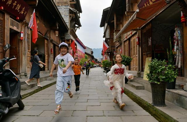 """6月8日,四川广元旺苍县""""中国红军城""""内,孩子们在玩耍。摄影/章轲"""