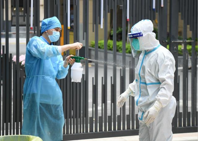 5月27日,在广州荔湾区白鹤洞街道一小区检测点,荔湾区骨伤科医院的医护人员给换班下来的同事喷洒消毒液。新华社图。