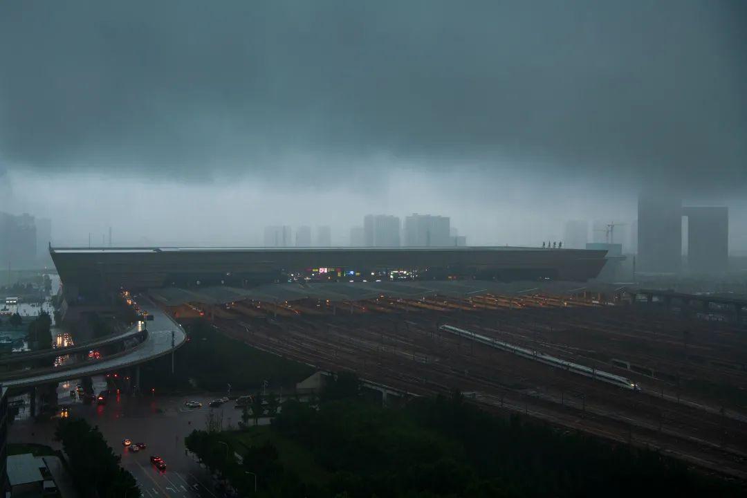 一列高铁在暴雨中驶离郑州东站