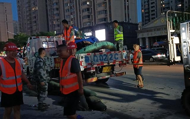 26日,山东东江抗洪救援队从车上卸下自购物资,继续帮助居民抽水。