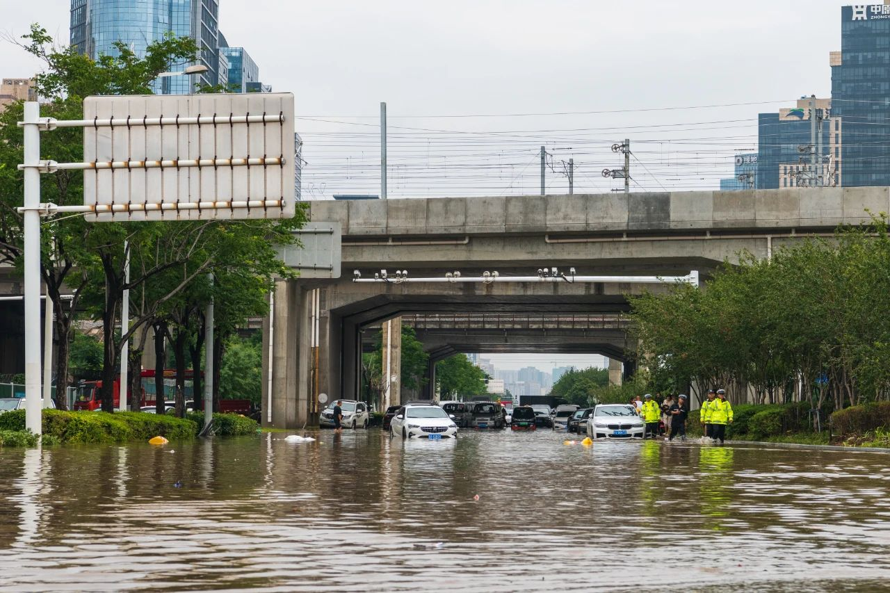 暴雨后,出现在郑州金水路与东三环路口引导交通的交警队伍