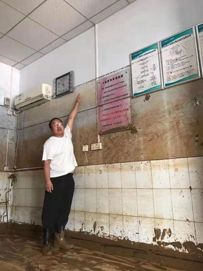 米河卫生院院长张遂升现场比划洪水漫过卫生院的高度。