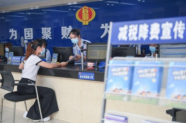 2020年9月22日,在国家税务总局福州市仓山区税务局办税服务厅,工作人员在辅导企业人员办理退税申报。新华社图。