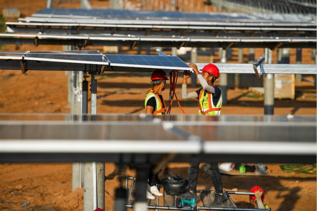 7月13日,工人为天骄绿能50万千瓦光伏发电项目安装光伏板。新华社图。