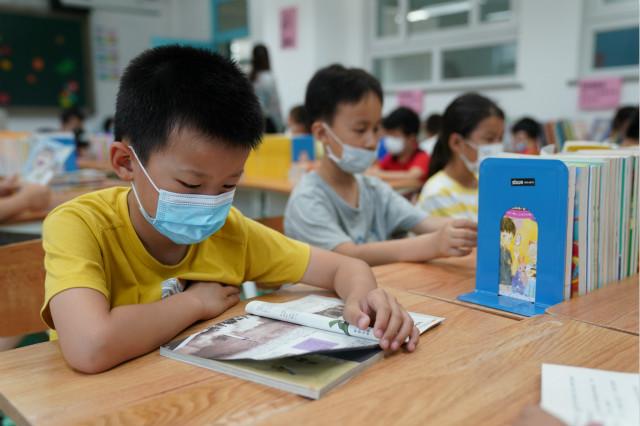 7月19日,孩子们在北京小学广外校区阅览室看书。新华社图。