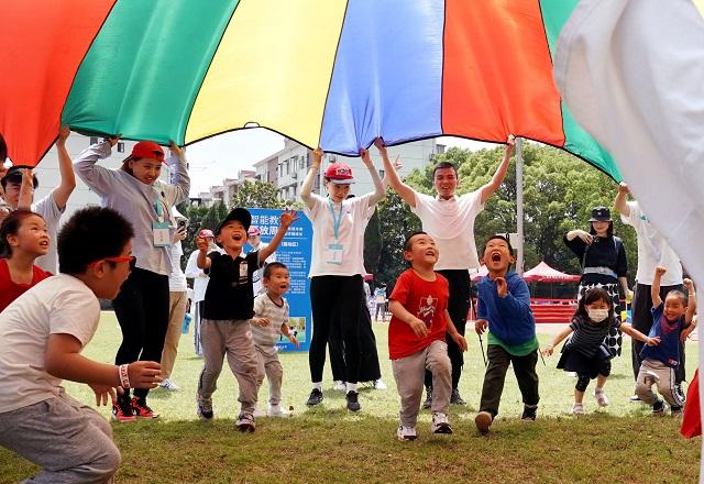 """5月29日,华东师范大学体育与健康学院师生带领小朋友们参与""""降落伞""""互动游戏。新华社图。"""