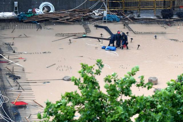 7月20日,工作人员在郑州市一建筑工地排水。新华社图。