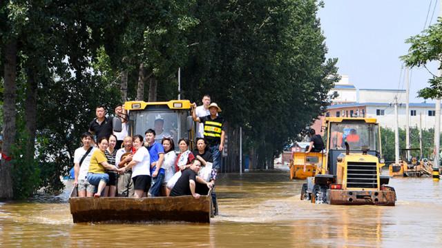 在新乡市凤泉区大块镇,志愿者驾驶铲车转运被困群众。 新华社图