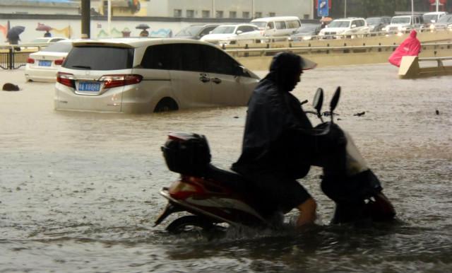 7月20日,郑州市民涉水骑行。新华社图。
