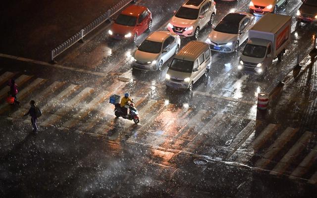 在天津市南开区,外卖骑手在风雨中骑行过马路。新华社资料