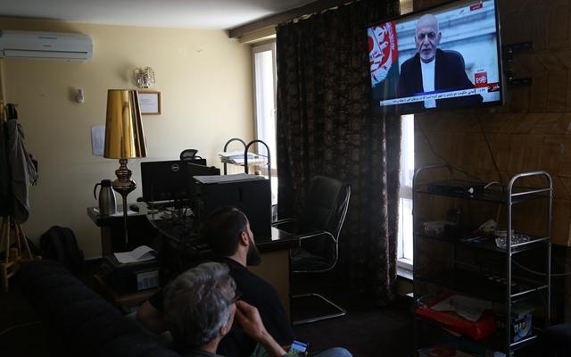 8月14日,人们在阿富汗首都喀布尔不雅旁观阿富汗总统添尼的电视说话。