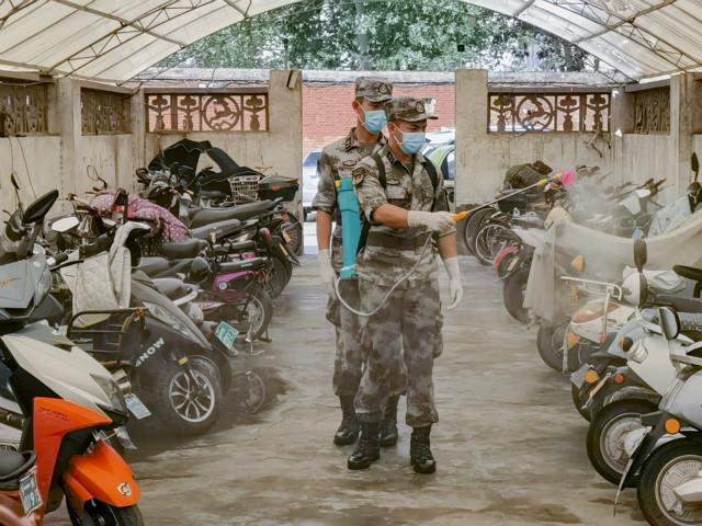 7月25日,郑州联勤保障中心某汽车团官兵在郑州市农业路开展防疫消杀工作。新华社图。