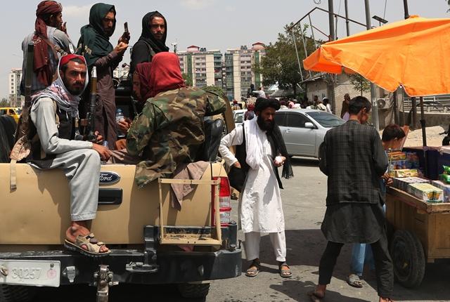 8月17日,阿富汗塔利班成员在喀布尔街头向小贩购物。