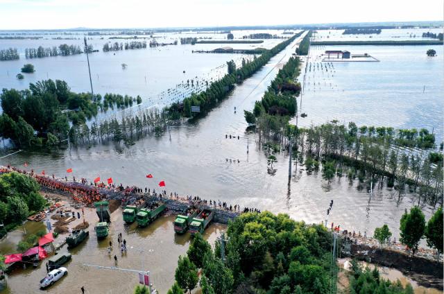 7月29日,在河南省鹤壁市浚县傅庄堤上,救援人员和群众一起填装沙袋,加固大堤(无人机照片)。新华社。