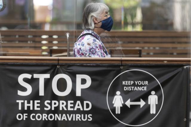 7月19日,一名戴口罩的女子从英国伦敦考文特花园的一处安全提示牌旁走过。新华社。