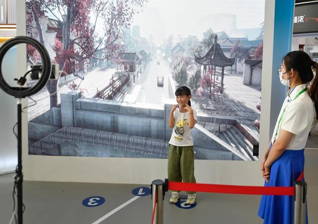 """9月25日,小朋友在""""互联网之光""""博览会上体验""""时间折叠""""AI(人工智能)互动项目。"""