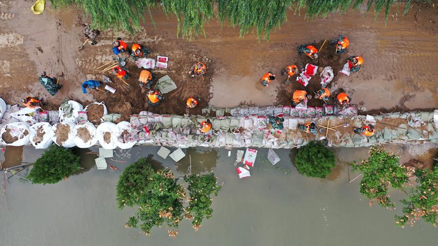 (在山西省河津市阳村街道连伯村,抢险人员在加固临时堤坝。图片来源:新华社)