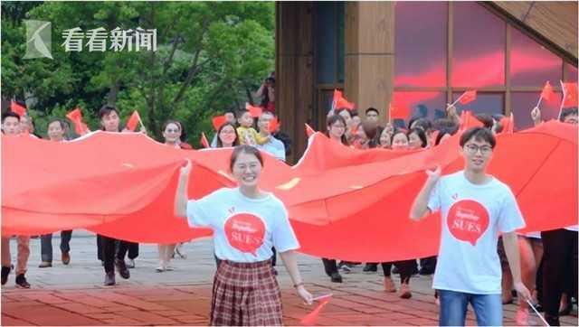 巨幅国旗在大学生护旗手的护送下进入广场