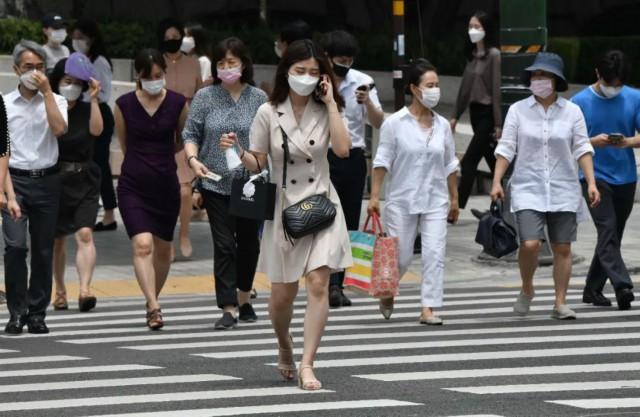 6月23日,戴口罩的行人在韩国首尔市中心过马路。韩国中央防疫对策本部本部长郑银敬22日表示,韩国首都圈地区正在经历新冠疫情的第二波扩散,要充分做好与疫情长期作战的准备。新华社/法新