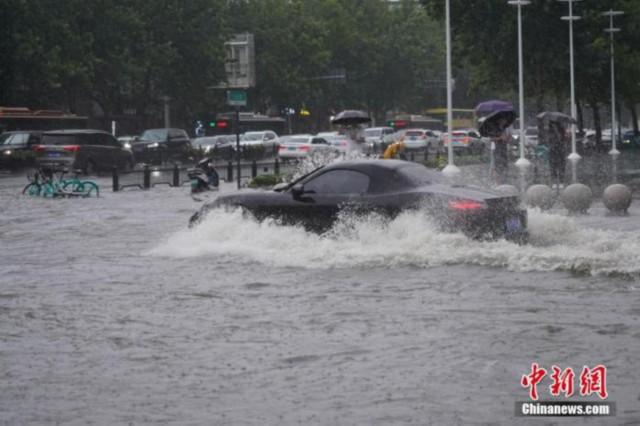 资料图:7月20日,河南郑州,车辆经过积水路段。<a target='_blank'  data-cke-saved-href='http://www.chinanews.com/' href='http://www.chinanews.com/'><p  align=